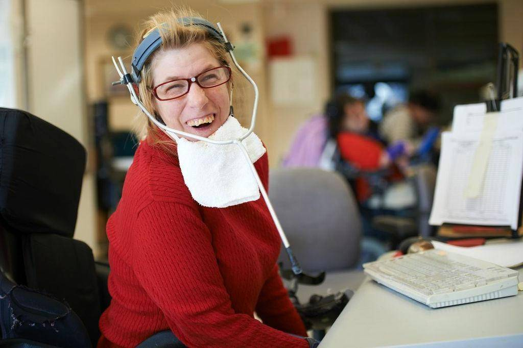 A woman smiling while working on a computer