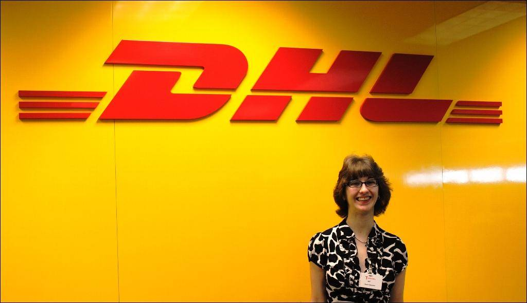A Redwood client standing in front of a DHL shipping sign.