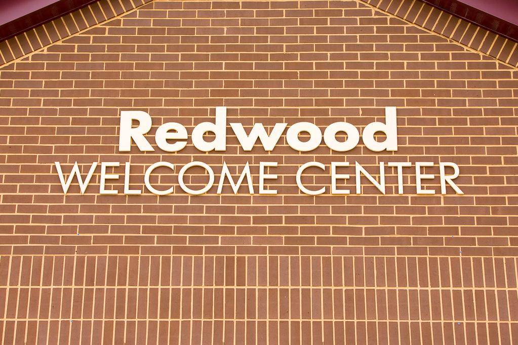 The Redwood Welcome Center sign on a building.