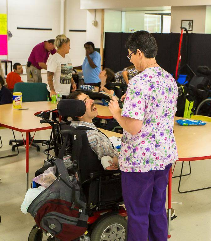 A woman in purple scrubs talking to a man in an electric wheelchair.