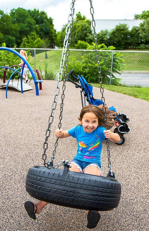 A young girl on a tire swing.
