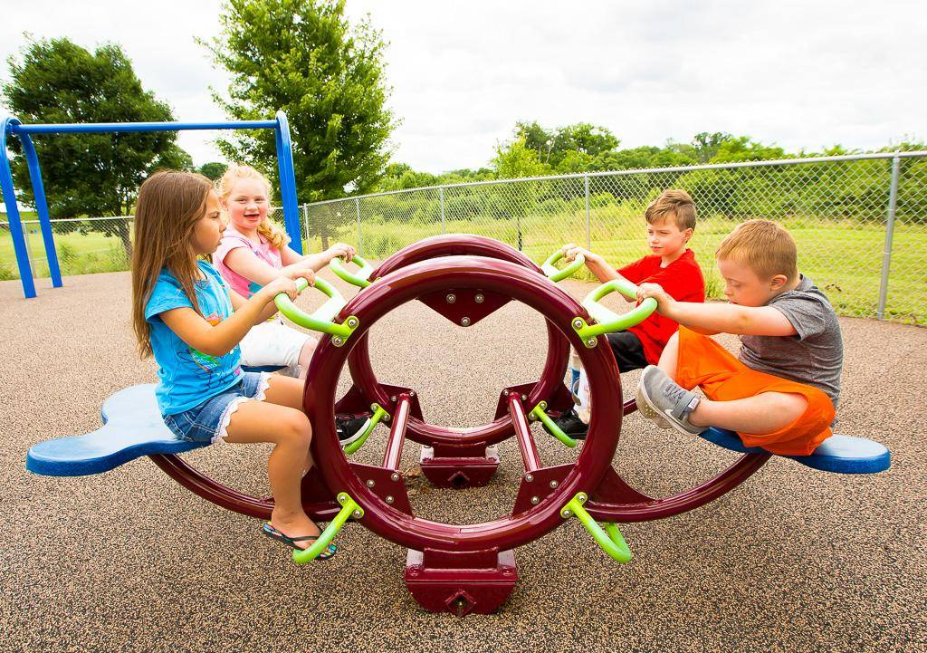 Four kids sitting and playing on playground equipment