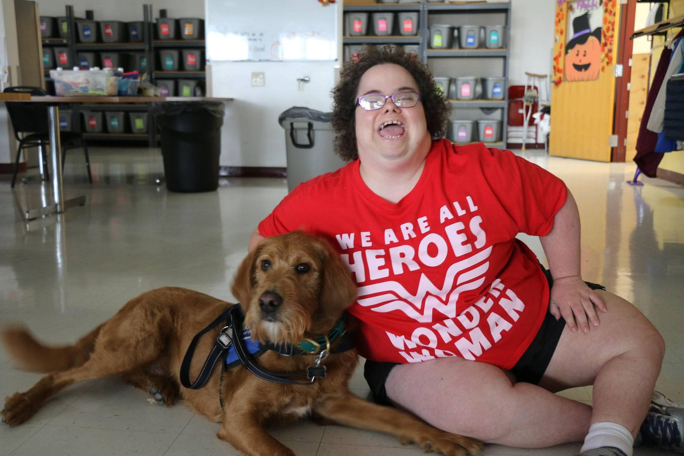 Women sitting on floor in red shirt with a dog