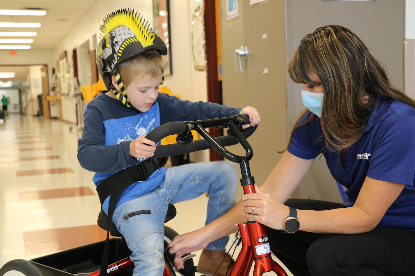 A Redwood employee assisting a child on a tricycle