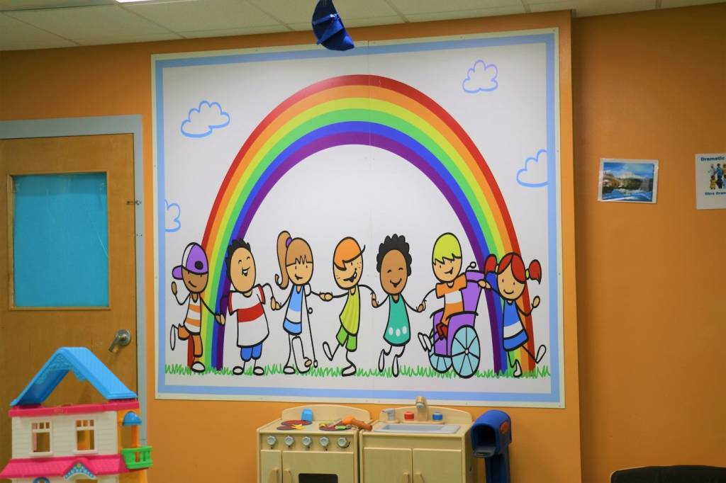 A poster on the wall at Redwood with children holding hands.