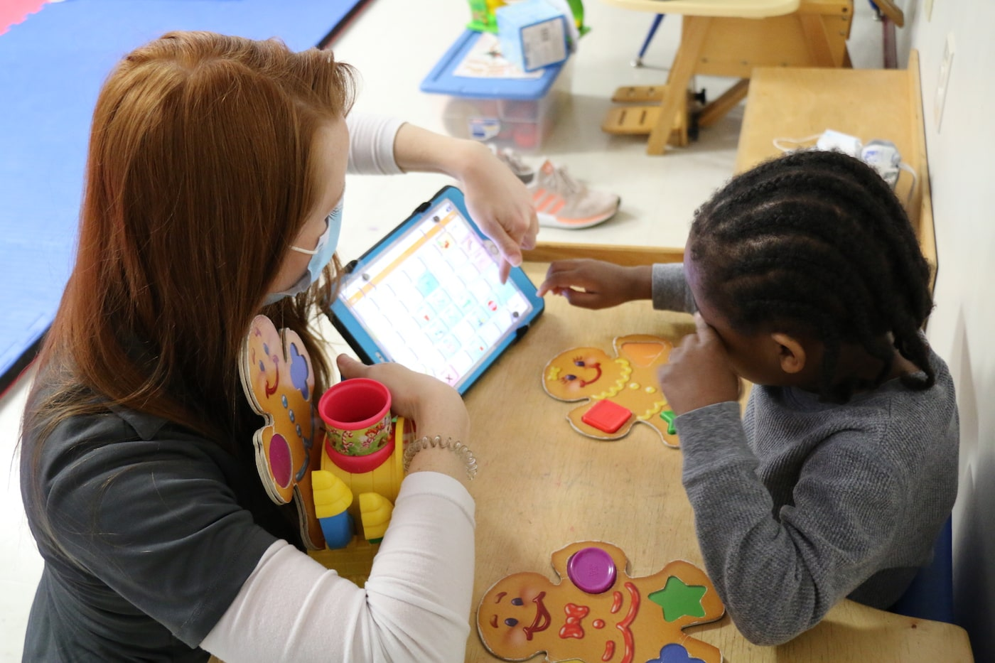 A Redwood employee working with a child on a tablet.